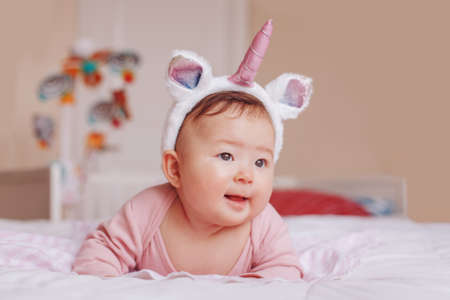 Portrait of cute adorable Asian mixed race smiling baby girl four months old lying on tummy on bed in bedroom wearing unicorn headband horn and ears. Childhood diversity lifestyle 写真素材