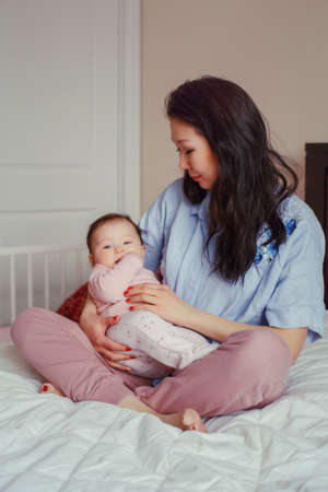 Portrait of beautiful mixed race Asian mother holding touching embracing her cute adorable newborn infant baby. Early development and health care lifestyle concept. Family in bedroom