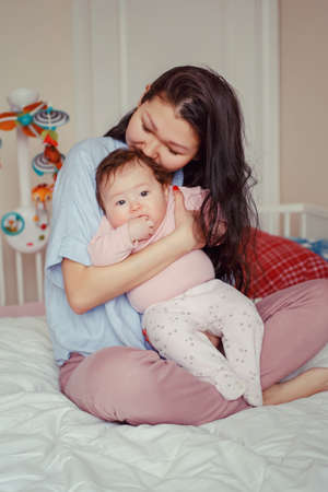 Portrait of beautiful mixed race Asian mother kissing touching embracing her cute adorable newborn infant baby. Early development and health care lifestyle concept. Family in bedroom