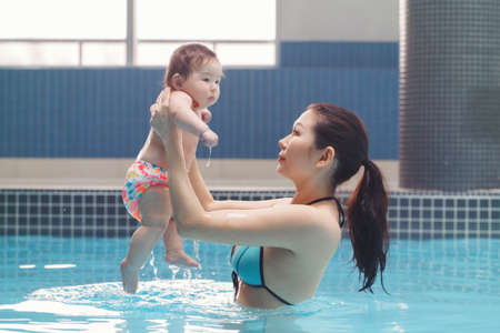 Mixed race asian mother holding her newborn baby in swimming pool standing in water. Mom with little child son daughter. Healthy active lifestyle. Family activity and bonding