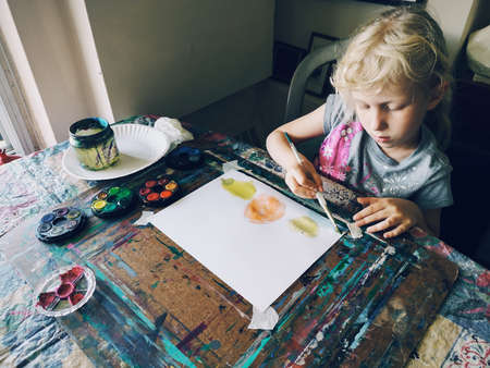 Caucasian preschooler girl sitting in art studio concentrated on painting fruits with brushes and water color paints. Children hobby activity.