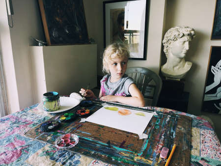 Toronto, Ontario, Canada - June 3, 2019: Caucasian preschooler girl sitting in art studio concentrated on painting fruits with brushes and water color paints. Children hobby activity. Stock fotó
