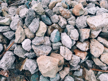 Closeup of small grey beige blue pink red broken crushed stones rocks lying on ground under rain. Natural environmental background texture. Garden rubble macadam top overhead view.