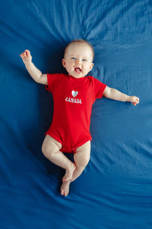 White Caucasian smiling baby boy girl with blue eyes lying on bed at home on Canada Day. Newborn infant child in red onesie romper celebrating national holiday July 1. View from top above Stock Photo