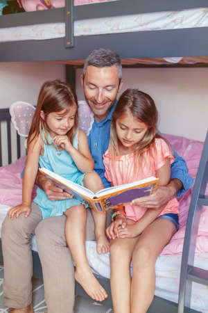 Family of three members people sitting on bed in bedroom reading book. Father and daughters girls at home spending time together. Parent talking communicate to children. Real people lifestyle Stock Photo
