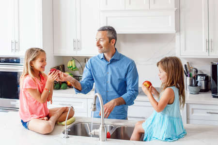 Caucasian father dad gives children daughters fresh fruits to eat. Happy family in kitchen eating. Organic food and healthy delicious tasty snack for kids. Lifestyle authentic real moment.