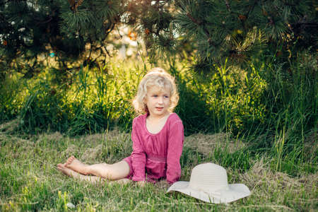 Portrait de jolie belle blonde fille caucasienne en robe rose rouge avec des cheveux en désordre assis sur l'herbe au sol dans le parc en plein air au coucher du soleil. Heureux adorable enfant aux pieds nus profitant de l'été.