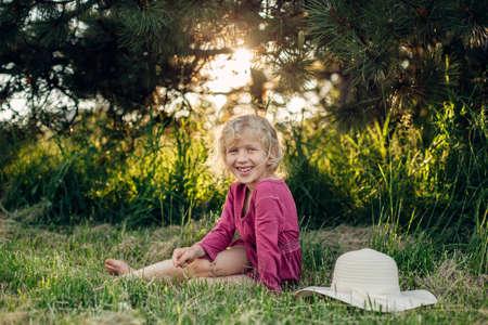 Porträt des netten schönen blonden kaukasischen Mädchens im roten rosa Kleid mit dem unordentlichen unordentlichen Haar, das auf dem Bodengras im Park im Freien bei Sonnenuntergang sitzt. Glückliches entzückendes barfüßiges Kind, das die Sommerzeit genießt.