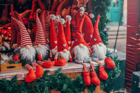 Colorful red toys dwarfs gnomes in red caps hats sitting on counter at traditional holiday Christmas market outdoors. Popular attraction for winter celebration activities.