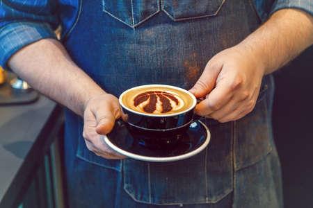 Toronto, Ontario, Canada - June 6, 2019: Closeup of barista hands holding black cup of coffee cappuccino with Toronto Raptors basketball team logo sign on milk foam. 報道画像