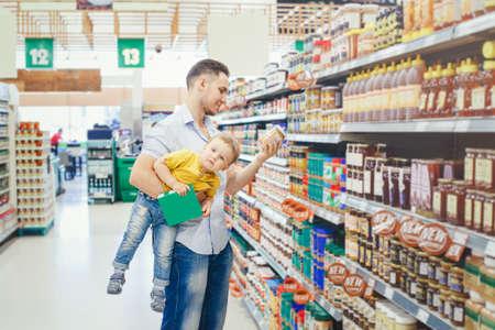 Papa père caucasien dans une épicerie, acheter de la nourriture et tenir son bébé sous le bras. Parent d'homme avec un enfant en bas âge choisissant un repas pour le dîner-déjeuner. Moment authentique de parentalité difficile.