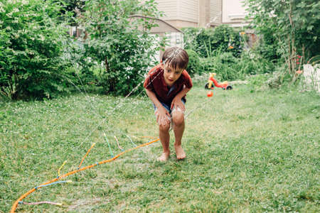 Preschool kid boy splashing with gardening hose sprinkler on backyard during summer day. Child playing with water outside at home yard. Candid authentic real life moment of funny family activity.