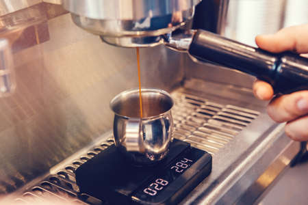 Closeup of professional cappuccino espresso machine making coffee. Thin hot drink liquid stream flow coming pouring to metal mug jug standing on scale. Toned with warm yellow film filters.
