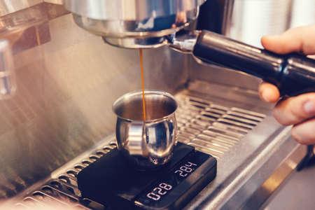 Nahaufnahme der professionellen Cappuccino-Espressomaschine, die Kaffee macht. Dünner Heißgetränk-Flüssigkeitsstrom fließt in einen auf der Skala stehenden Metallbecherkrug. Getönt mit warmen gelben Filmfiltern.