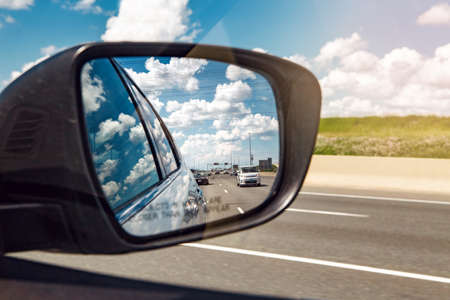 Closeup of rear back car mirror with beautiful landscape midday view of  Toronto city highway street road. Cars traffic during sunny day with white clouds in blue sky reflected in vehicle glass.