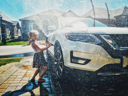 Cute preschool little Caucasian girl washing car on driveway in front house on sunny summer day. Kids home errands duty chores responsibility concept. Child playing with hose spraying water. 写真素材