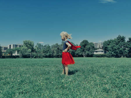 Portrait of cute adorable lonely sad unhappy little young Caucasian girl child in super hero dress with cape waving in wind standing alone in large field meadow outdoors on summer day.