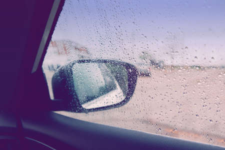 Blurry wet abstract glass background. Rear back view car mirror with rain drops during rainy bad weather. Sadness loneliness concept. Toned with retro vintage violet purple filters. Banco de Imagens