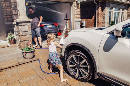 Cute preschool little Caucasian girl helping father wash car on driveway in front house on summer day. Child wiping cleaning machine bumper. Kids home errands duty chores responsibility concept.