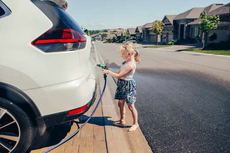 Cute preschool little Caucasian girl washing car on driveway in front house on sunny summer day. Kids home errands duty chores responsibility concept. Child playing with hose spraying water. Banco de Imagens