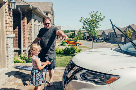 Cute preschool little Caucasian girl child helping father wash car with water from hose on driveway in front house on sunny summer day. Kids home errands duty chores responsibility concept. Banco de Imagens