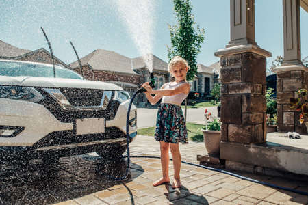 Cute preschool little Caucasian girl washing car on driveway in front house on sunny summer day. Kids home errands duty chores responsibility concept. Child playing with hose spraying water. Imagens