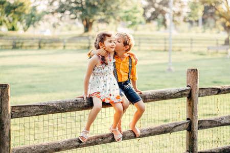 Twee leuke grappige blanke kinderen jongensmeisje zittend op het hek in het park buiten. Vrienden broers en zussen kinderen knuffelen zoenen bij zonsondergang in de zomer. Romantische liefde en vriendschap natuurlijke levensstijl authentiek moment. Stockfoto