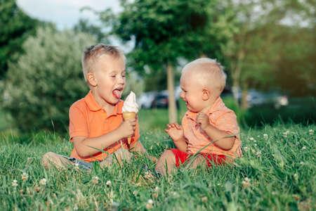 Zwei kaukasische lustige Kinderjungengeschwister, die zusammen sitzen und essen, die ein Eis teilen. Kleinkind jüngeres Baby weint und älterer Bruder, der ihn neckt. Liebe Neid eifersüchtige Brüder Freundschaft.