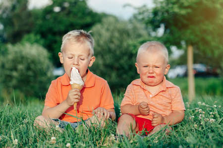 Two Caucasian funny children boys siblings sitting together eating sharing one ice-cream. Toddler younger baby crying and older brother teasing him. Love envy jealous brothers friendship. Фото со стока