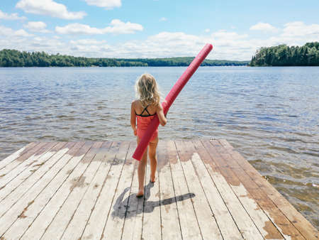 Caucasian preschool blonde girl in pink swimsuit standing on wooden lake river dock with pool noodle on summer day. Happy healthy active lifestyle childhood. View from back behind. Stok Fotoğraf