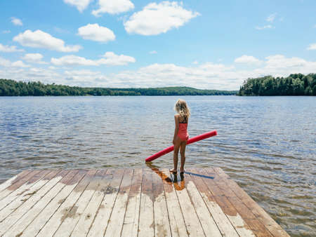 Caucasian preschool blonde girl in pink swimsuit standing on wooden lake river dock with pool noodle on summer day. Happy healthy active lifestyle childhood. View from back behind. Imagens
