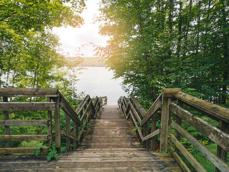 Beautiful landscape day view at Canadian Ontario Kettles lake in Midland with wooden staircase to water. Canada forest nature. Amazing summer scene with green trees, sunlight and flare. Stock Photo