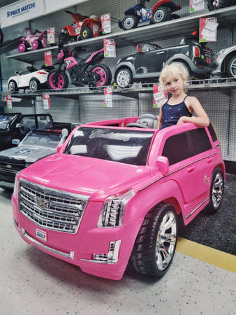 Toronto, Ontario, Canada - July 08, 2019: Cute adorable preschool blonde Caucasian girl sitting posing in large huge pink Cadillac car in kids children store Toys Are Us. Happy childhood lifestyle.