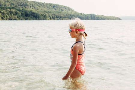Cute adorable Caucasian girl swimming in lake river with underwater goggles. Child diving in water on beach. Authentic real lifestyle happy childhood. Summer fun outdoor aquatic activity.