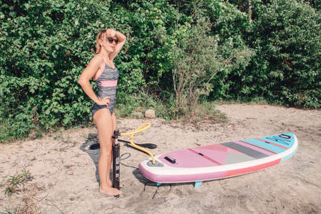Beautiful Caucasian blonde woman inflates sup surfboard with pump on beach. Summer nature outdoor individual aquatic sport activity. Healthy lifestyle concept. Banco de Imagens