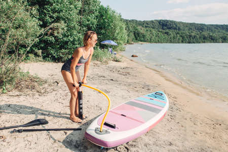 Beautiful Caucasian blonde woman inflates sup surfboard with pump on beach. Summer nature outdoor individual aquatic sport activity. Healthy lifestyle concept. Reklamní fotografie