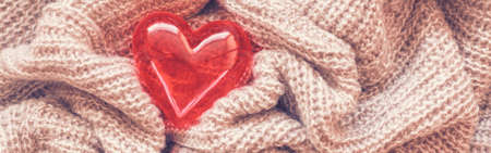Closeup macro of knitted wool fabric material with red shiny smooth heart. Clothing texture background with wrinkles and folds. Valentine holiday love card. Web banner for website header. Banco de Imagens