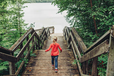 Preschool Caucasian girl walking down wooden stairs to water at Canadian Ontario Kettles lake in Midland. Canada forest nature. Amazing landscape with green trees. View from back. 版權商用圖片