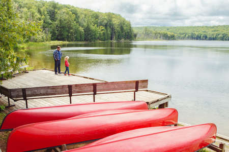 Father and daughter girl at Canadian Ontario Kettles lake in Midland area. Canada forest park nature with red kayaks canoe boats by water. Summer seasonal family recreational sport activity.