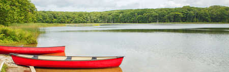 Beautiful landscape summer scene at Canadian Ontario Kettles lake in Midland area. Canada forest park nature with red kayaks canoe boats by water. Web banner header for website.