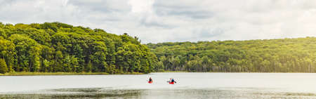 Canada forest park nature with family friends riding in red kayaks canoe boats in water. Beautiful landscape scene at Canadian lake river area. Web banner header for website.