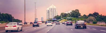 Night traffic. Cars on highway road at sunset evening in typical busy american city. Beautiful amazing urban view with red, yellow sky. Sundown in downtown. Web header banner for website.