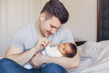 Young Caucasian father dad with his newborn mixed race Asian Chinese baby. Male man parent holding child daughter son. Authentic lifestyle touching tender moment. Single dad family.