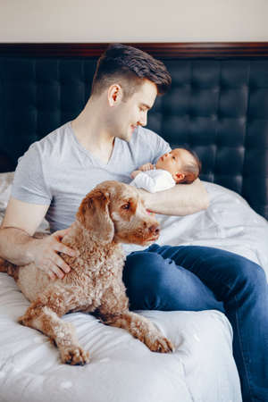 Portrait of young Caucasian father with mixed race Asian Chinese newborn baby. Dog pet lying on bed. Man parent holding child daughter son. Authentic lifestyle moment. Single dad family life.