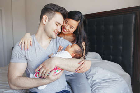 Portrait of beautiful smiling Chinese Asian mother and Caucasian father with mixed race newborn infant baby son daughter. Happy family in bedroom. Home lifestyle authentic natural moment. Banco de Imagens