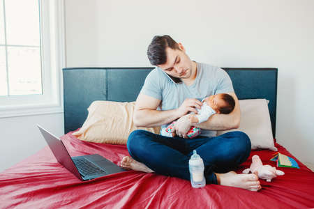 Caucasian father dad with newborn mixed race Asian Chinese baby working from home. Male man parent holding child daughter son talking over phone. Single dad family. Genderblend concept