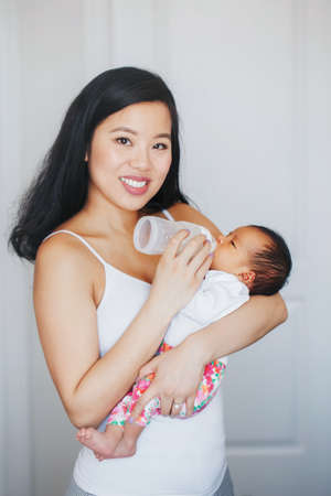 Portrait of young Chinese Asian mother feeding newborn baby son daughter with milk formula from bottle. Authentic lifestyle candid real moment. Real motherhood family life concept.