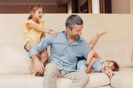 Father and daughters girls kids at home spending time together. Parent playing with children. Family having fun hugging and laughing. Real people lifestyle.  Fathers day holiday concept.
