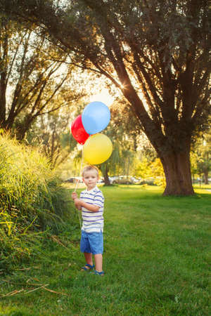 Cute adorable little Caucasian boy toddler child with colorful balloons in park outdoor. Kid enjoying playing. Happy birthday holiday celebration. Candid authentic lifestyle childhood moment.