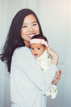 Portrait of beautiful smiling Chinese Asian mother holding cute adorable newborn infant baby girl daughter. Happy family in bedroom. Home lifestyle authentic natural moment. Mothers day.